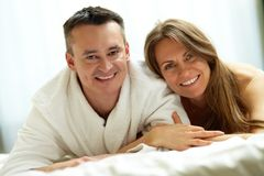 Closeness. Happy couple lying in bed and looking at camera with smiles Royalty Free Stock Photography