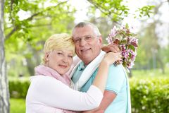 Closeness. Happy mature couple embracing and looking at camera outside Stock Photography