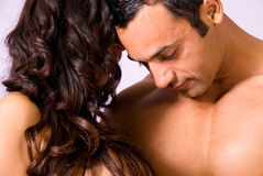 Closeness. Close up of a latino man, with his partner, her face can't be seen ,only her long wavy hair royalty free stock images