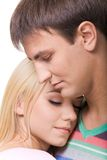 Closeness. Pretty girl keeping close to handsome guy with loving expression on their faces Stock Image
