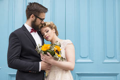 Closeness. Newlywed couple standing next to a blue retro wooden door, holding a sunflower wedding bouquet and hugging royalty free stock photos