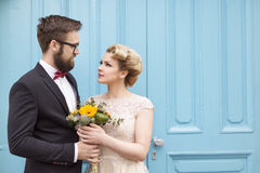 Closeness. Newlywed couple standing next to a blue retro wooden door, holding a sunflower wedding bouquet and looking at each other royalty free stock image