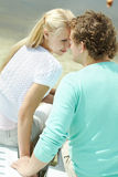 Closeness. Photo of amorous couple sitting on deck chairs face to face Royalty Free Stock Image