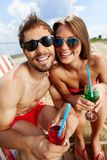 Closeness. Relaxed young couple with refreshing drinks sitting on beach Stock Images