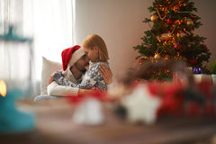 Closeness. Young couple embracing on Christmas night at home Royalty Free Stock Images