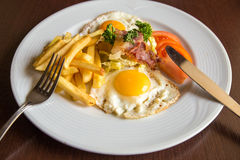 Closep  breakfast  with fried potato bacon eggs. And tomato on  a plate Royalty Free Stock Photos