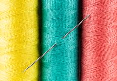 Closep colorful sloops of threads and a needle Royalty Free Stock Image