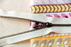 A zipper on sweet color fabric background. Royalty Free Stock Photo
