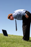 Closer Look at the Business. Young man bends over to look at laptop screen against blue, cloudless sky and on green, grassy lawn stock photo