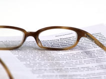 A Closer look at Marketing Research. Glasses sitting on a page focusing on Marketing Research stock images