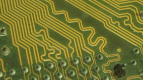 Closer Macro Camera Dolly across computer circuit board. Move diagonally past soldered patterned row of circuit terminals;pause t stock footage