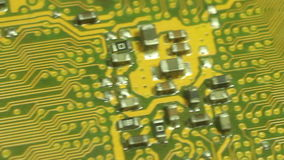 Closer Macro Camera Dolly across computer circuit board.Start from central circuit cluster area, then move diagonally along etche stock footage