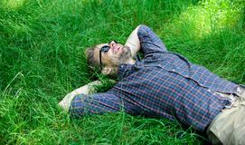 Closer to nature. Man bearded hipster united with nature. Nature fills him with freshness and inspiration. Man unshaven. Guy lay on green grass meadow. Guy stock image