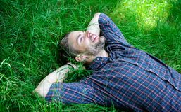 Closer to nature. Nature fills him with freshness and inspiration. Man unshaven guy lay on green grass meadow. Guy happy. And peaceful enjoy freshness of grass royalty free stock photos