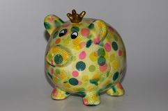 Closer view on a colorful piggy bank isolated on a wooden underground and white background. Photographed in multi colored and cut out and isolated royalty free stock image