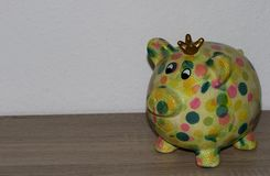 Closer view on a colorful piggy bank with a wooden underground and white background. Photographed in multi colored and cut out, copy space and isolated royalty free stock photography