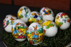Closer view on an easter egg with an easter bunny painting eggs with a brick wall in the background stock image