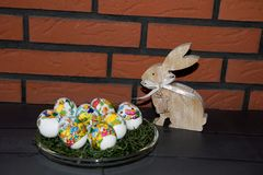 Closer view on easter eggs and a easter bunny in front of a brick wall. Photographed in the garden in germany during easter on a sunny spring day stock photos