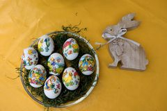 Closer view on easter eggs and a wooden easter bunny on a yellow tablecloth with copy space. And photographed in the garden in germany during easter on a sunny royalty free stock photography