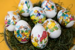 Closer view on easter eggs on a yellow tablecloth. And photographed in the garden in germany during easter on a sunny spring day stock photography