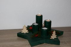 Closer view on a green advents wreath with two burning candles at home in niederlangen emsland germany. Photographed indoors with a white background and wooden stock images