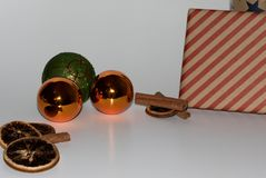 View on some orange and green christmas balls and christmas decoration and with two presents and with a white background and under. Closer view on some orange royalty free stock photo