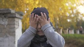 Closes eyes with hands. Smiling little baby boy playing in the park. Autumn. stock video footage