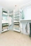 Closet. Large walk in closet with modern wardrobe on hangers royalty free stock photo