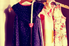 Closet with colorful baby dresses on hanger stock images
