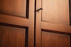 Closet door with a key. Wooden closet door with a metal key in a bedroom stock photo