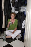 Closet Drinker Surprised. Female hiding in the closet with a bottle and a drink with a surprised expression Stock Image