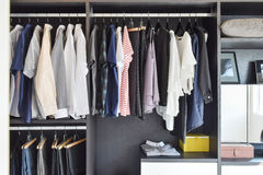 Closet with row of cloths hanging in black wardrobe. Modern closet with row of cloths hanging in black wardrobe stock images
