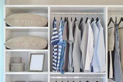 Closet with row of cloths hanging in white wardrobe royalty free stock photos