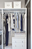 Closet with row of cloths hanging in white wardrobe stock images