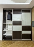 Closet with sliding doors. Modern closet with three sliding doors, made of laminated glass and plywood. One door is open in order to show interior of the closet stock images