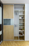 Closet with sliding doors. Modern closet with two sliding doors, made of laminated glass and plywood. One door is open in order to show interior of the closet royalty free stock photos