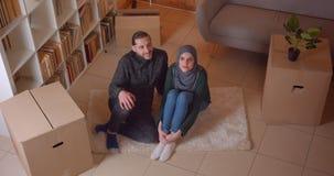 Closeupöverkantfors av unga lyckliga muslim par som sitter på golvet i en nyligen köpt lägenhet som glatt ler arkivfilmer