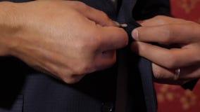 Концепция человека моды кнопка вверх по его кнопкам на его куртке, конец-вверх человека бизнесмен в утре кладет дальше работу clo акции видеоматериалы