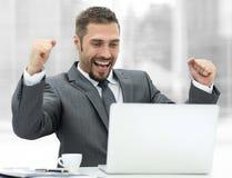 closeup счастливый бизнесмен сидя перед открытой компьтер-книжкой Стоковые Фотографии RF