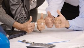 Closeup of 4 thumbs up in office stock images