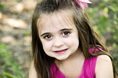Closeup. Beautiful brunette child smiling with big brown eyes and fair skin Stock Image