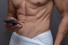 Closeup abs of man wrapped in towel as he texts on phone Royalty Free Stock Images
