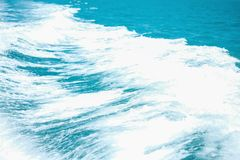 Closeup abstract wave caused by speed boat on blue sea textured background stock images