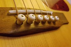 Acoustic Guitar Bridge, pegs, and strings Closeup. Closeup of an Acoustic Guitar Bridge, pegs, and strings royalty free stock images
