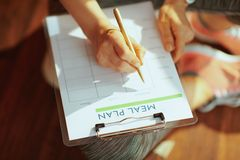Closeup on active woman with clipboard filling meal plan. Closeup on active woman in fitness clothes with clipboard filling meal plan in the modern house royalty free stock photo