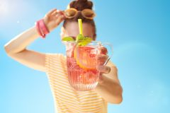Closeup on woman against blue sky holding refreshing cocktail Stock Photo