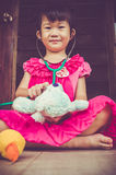 Closeup adorable asian girl playing doctor or nurse with plush t Royalty Free Stock Photography