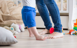Closeup of adorable baby`s and mother`s feet on floor at living Royalty Free Stock Photography