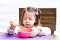 Hungry Girl Eating Food From Bowl. Closeup of adorable child having food with spoon at home stock photos