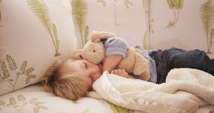 Closeup of an adorable sleepy young child lying on a sofa.  stock photos